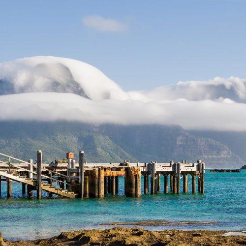 Across the lagoon towards the mountains nestled under a Cap Cloud